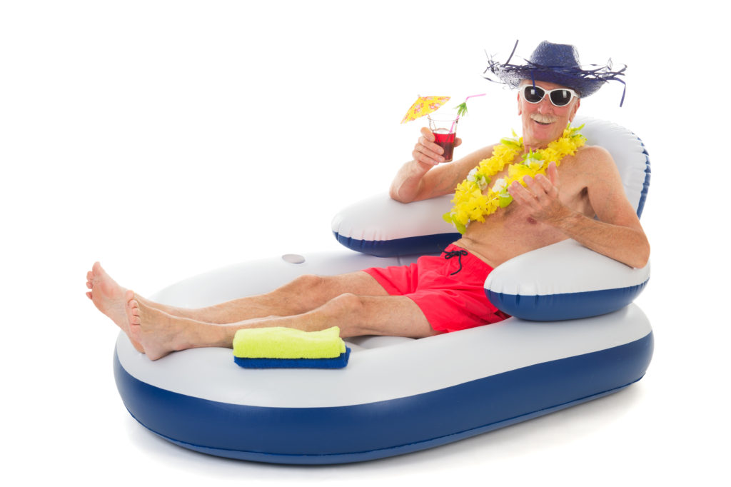 Senior man in beach hat and sunglasses enjoying a cold umbrella drink while sitting in a floating lounge.
