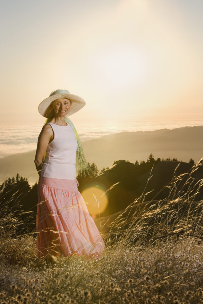 Senior woman in cute floppy hat wearing loose fitting top and long flowing skirt while standing in a grassy field at sundown.