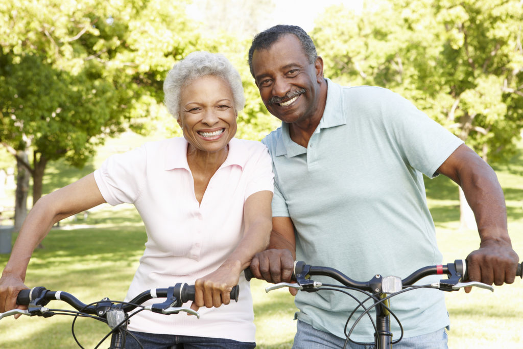 Healthy seniors ride bikes in sunny park.