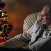 Elderly man quietly gazing at sparkling lights on small Christmas Tree.