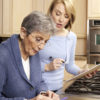 Senior woman fills medicine planner with help from a female caregiver.