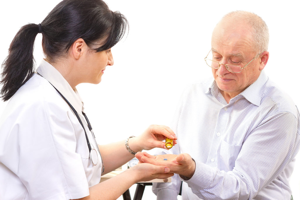 Senior man receiving medications from female healthcare professional