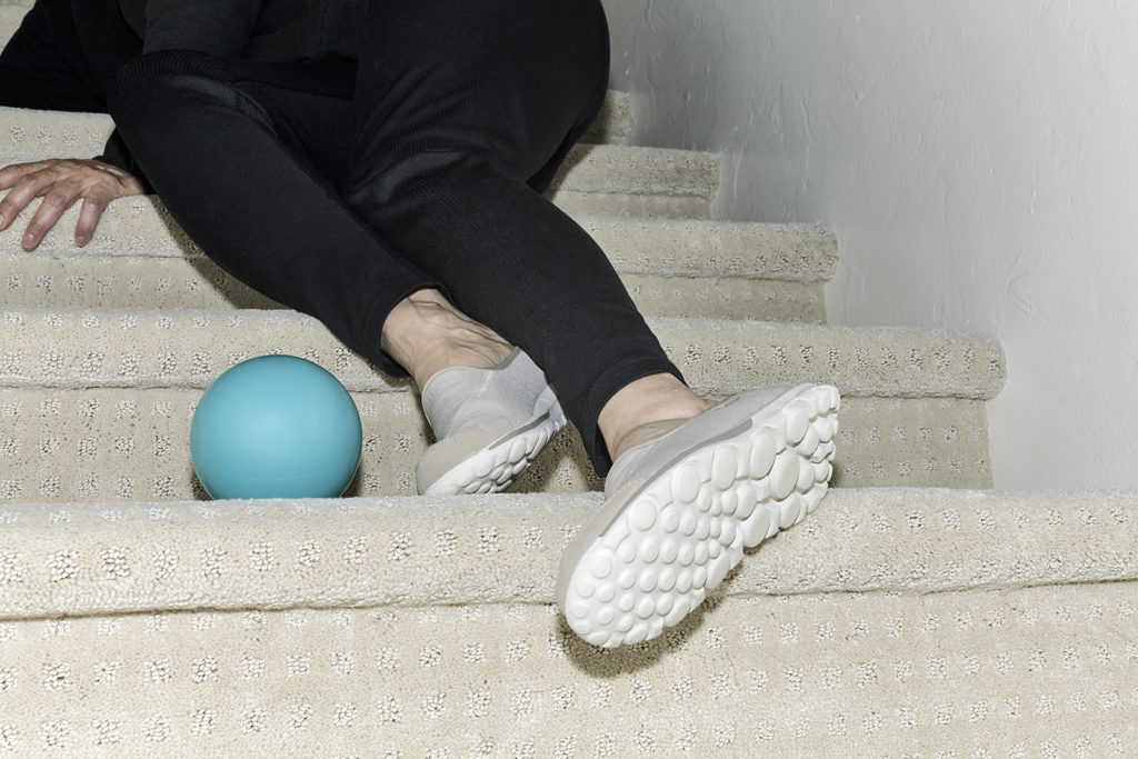 Woman's legs on carpeted stairwell with a recent fall having tripped over a ball on the steps.