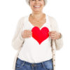 Smiling middle-age woman holding a paper heart silhouette.