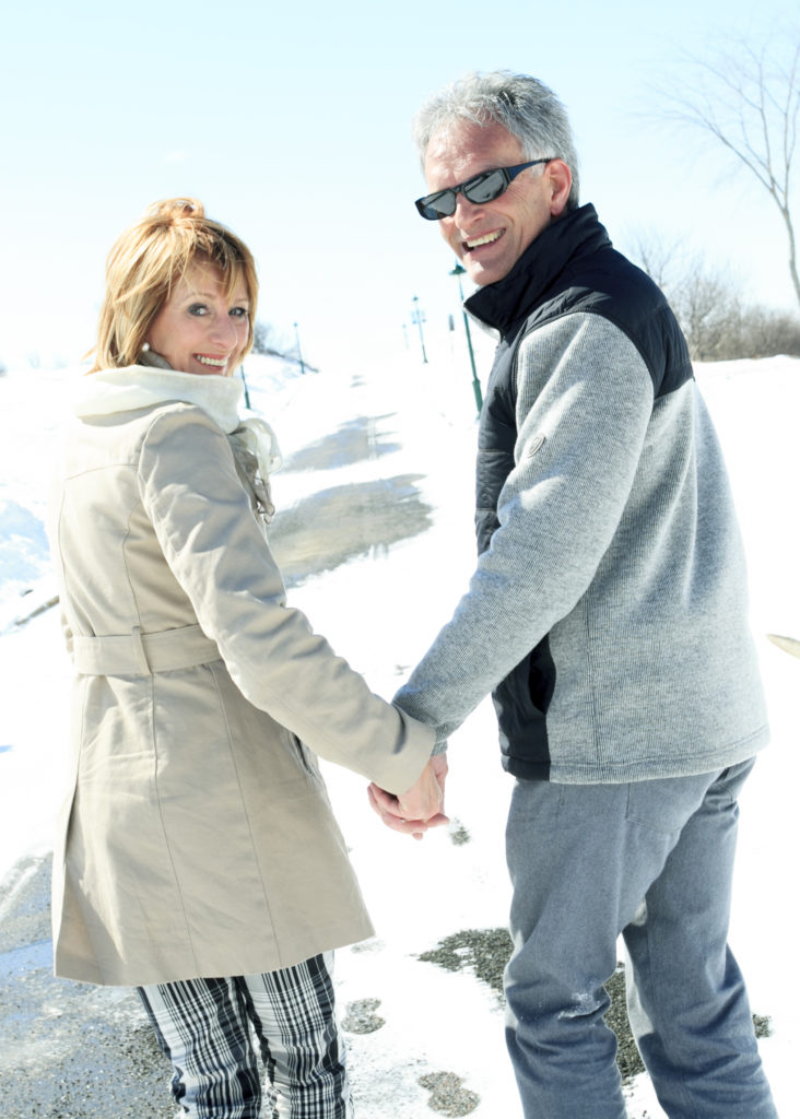 Happy senior couple walking together hand in hand on a sunny winter day.