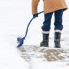 A man with a curved handled snow shovel clearing snow from a brick sidewalk in Canadian winter.