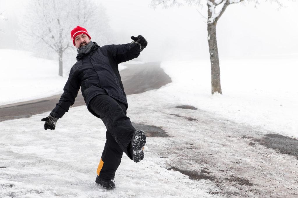 Man slips on icy walkway.