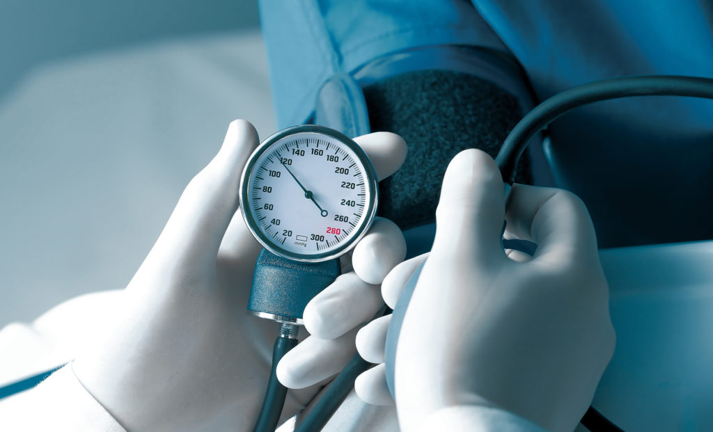 Clinician in white gloves measures blood pressure.