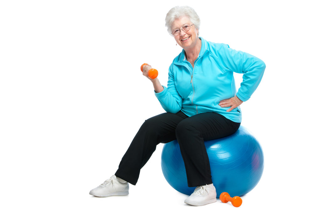 Smiling senior woman in fitness training with dumbbells