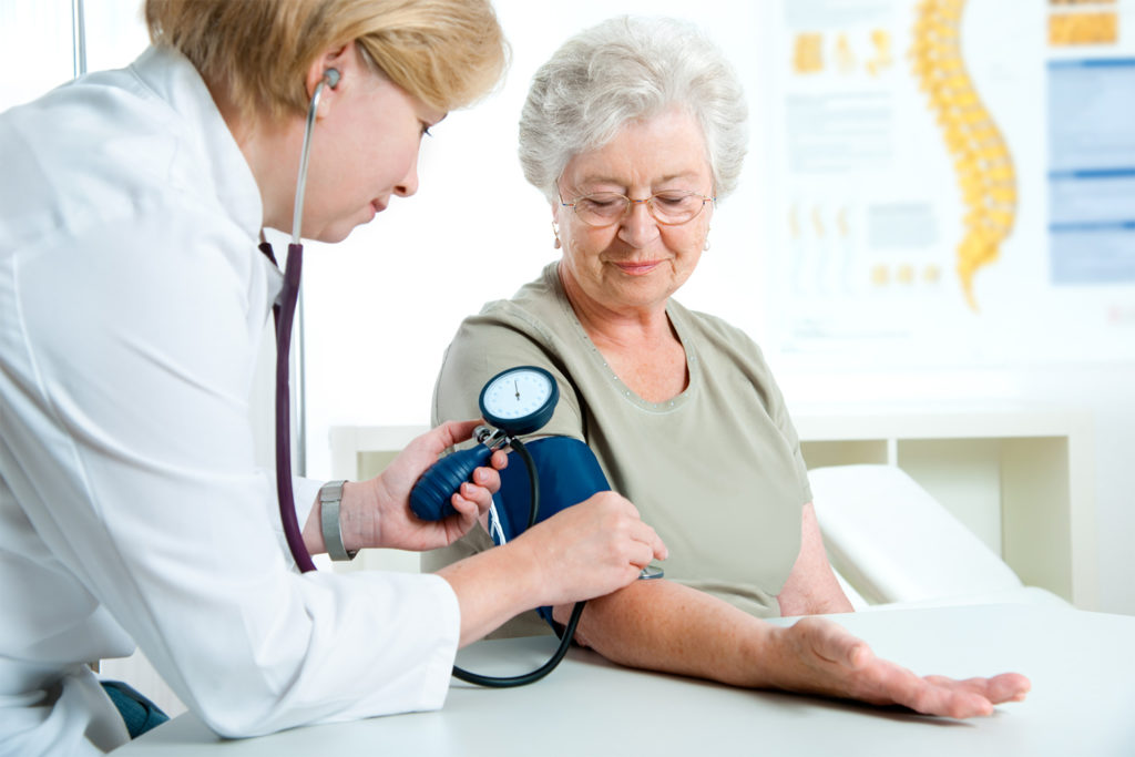 Nurse-clinician takes blood pressure reading of senior woman in medical office.