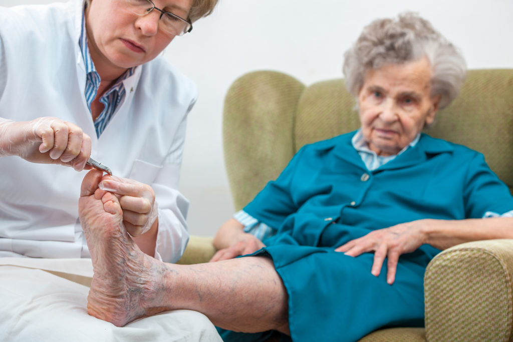Nurse provides professional foot care services for elderly woman in home.