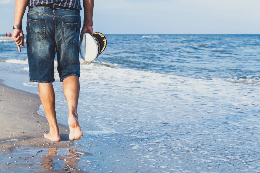 Senior man strolling barefoot on beautiful beach near blue ocean.