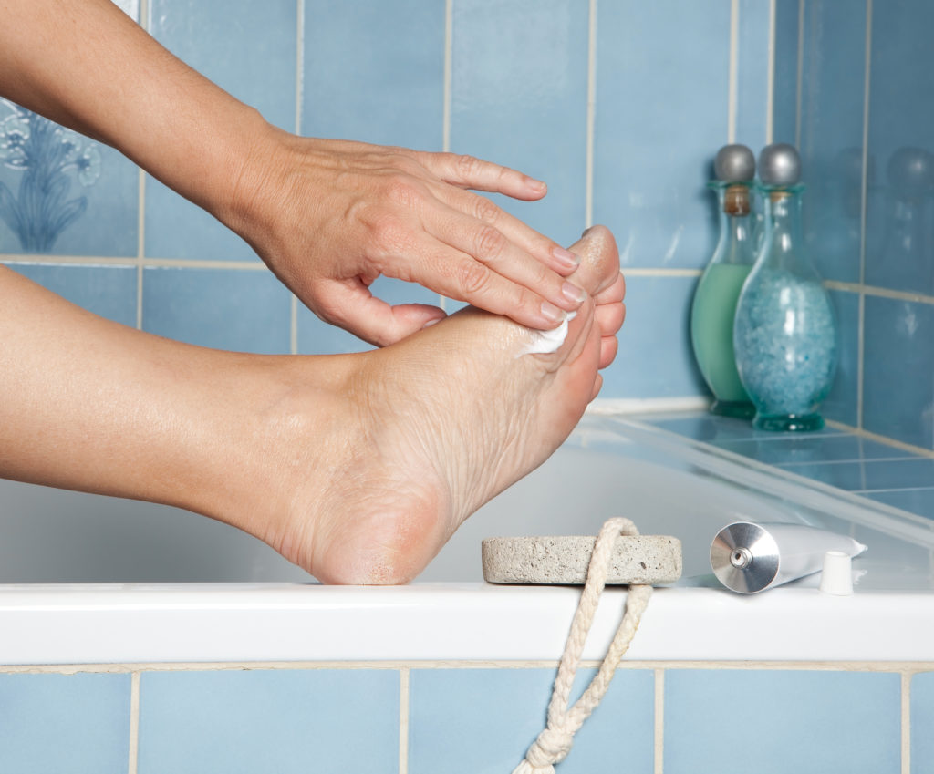 Woman's hand applying soothing lotion to freshly bathed feet in a blue bathroom.