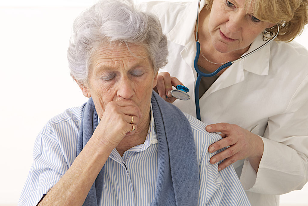 Elderly woman coughing during pulmonary exam with a pulmonologist.