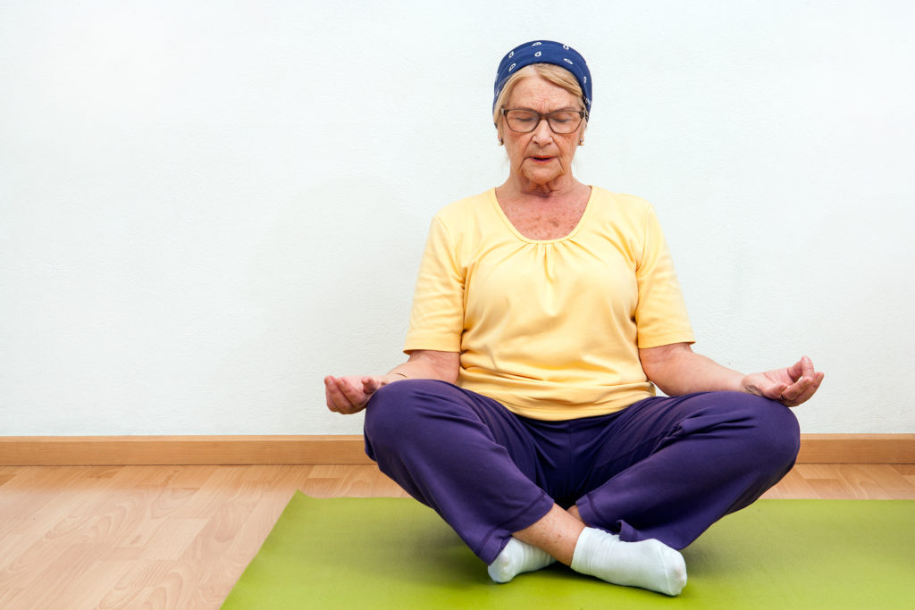 Elderly woman practicing yoga in gym.