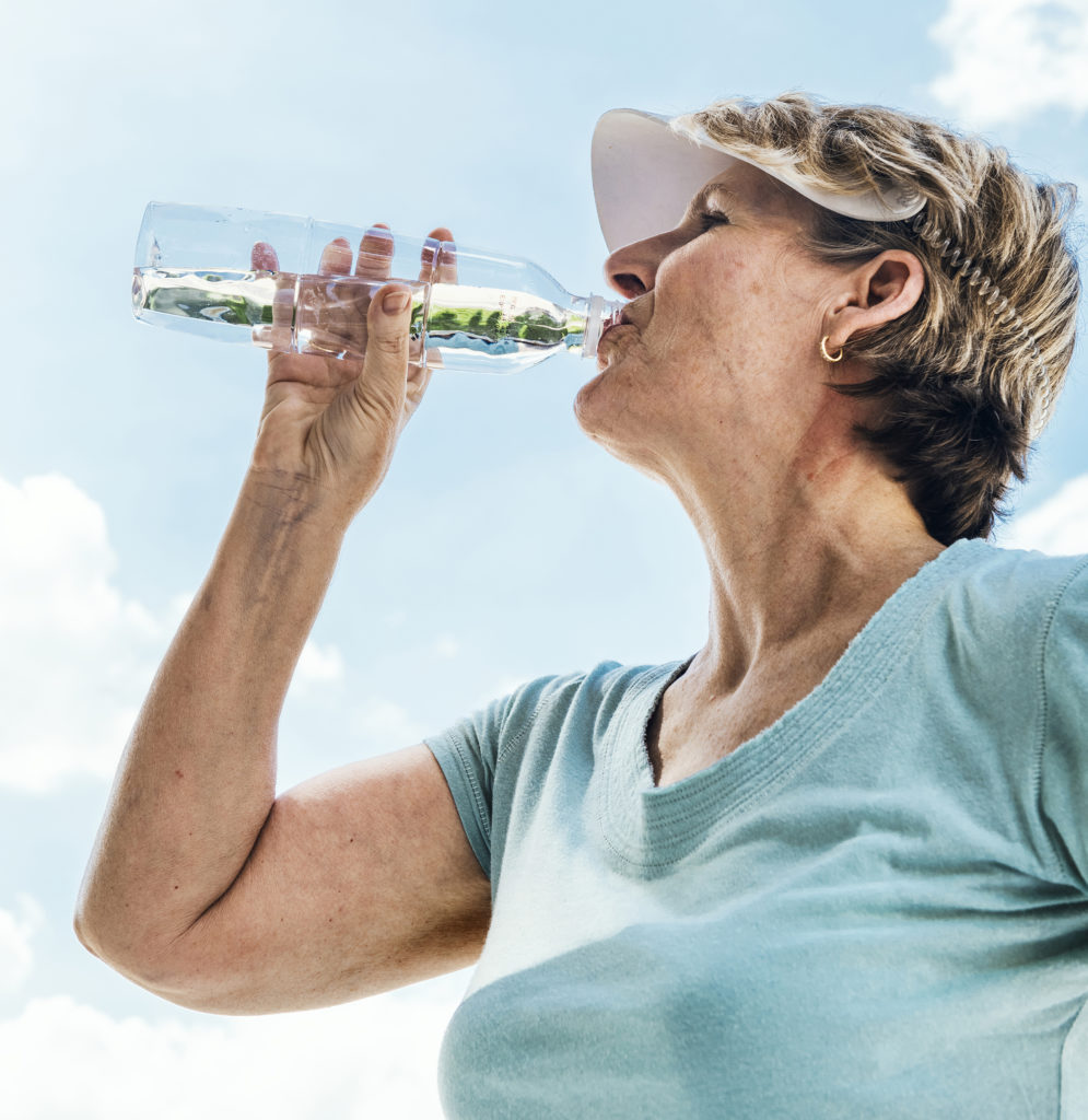 Older adult woman drinking water on a hot day after exercising.