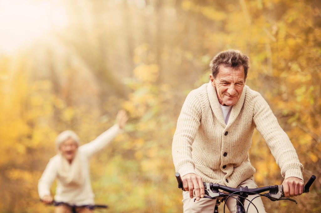 Seniors bicycling in autumn woods.