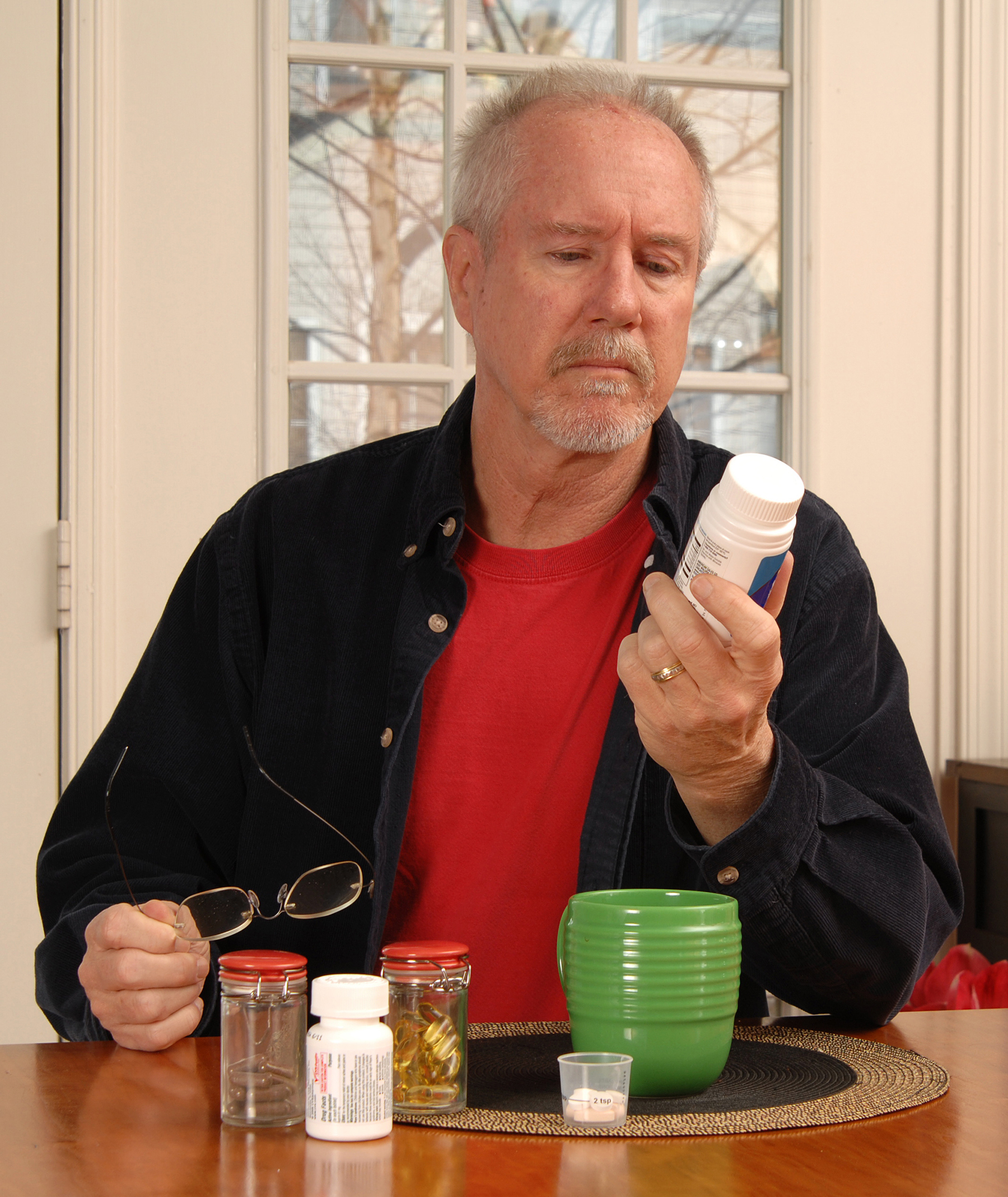 Senior man reading medication label at kitchen table.