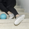 Woman's legs after falling on indoor carpeted stairs with child's ball near her feet.