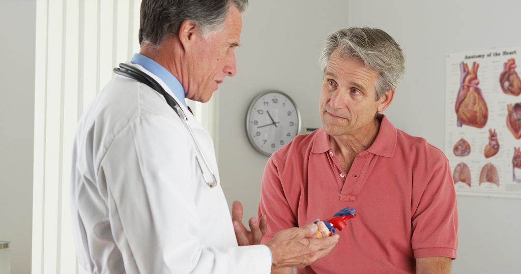 Cardiologist talking to patient in exam room.