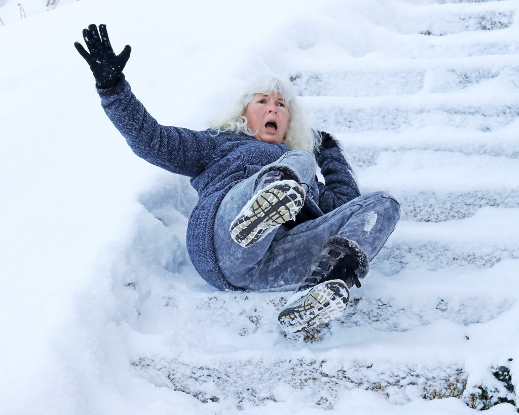 Senior woman accidentally slips on snow-covered steps outside.