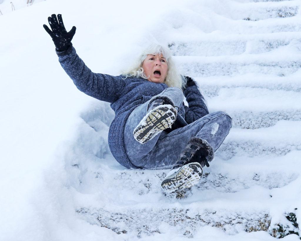 Senior woman accidentally slips on snow-covered steps outside.