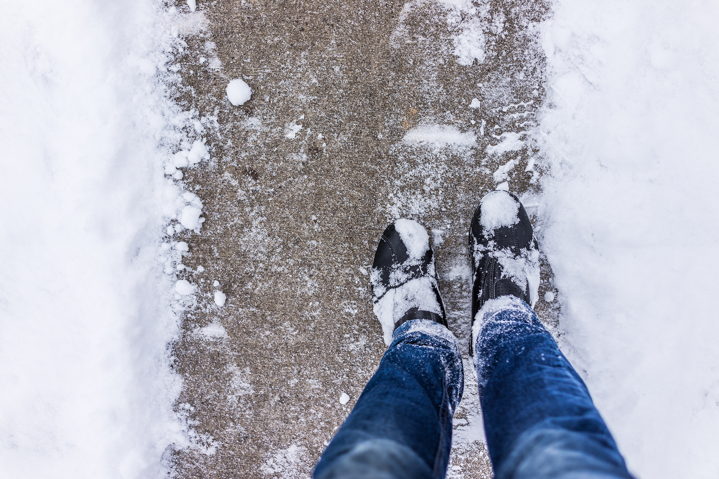 Looking down on a cleared path on snowy walkway with person in black boots