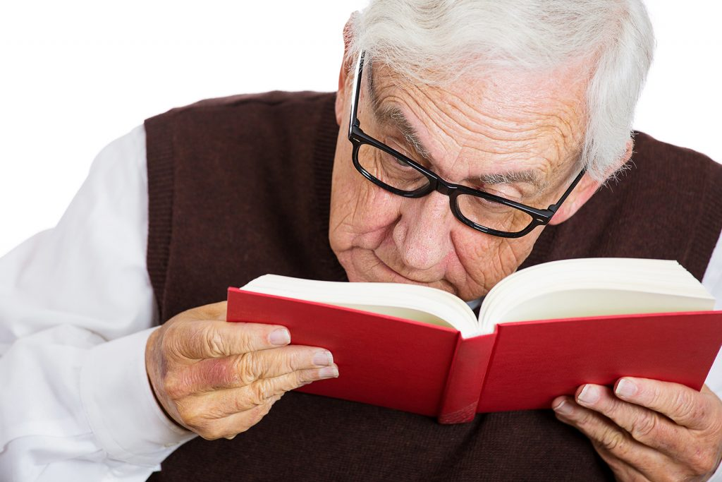 Senior man straining to read a book.
