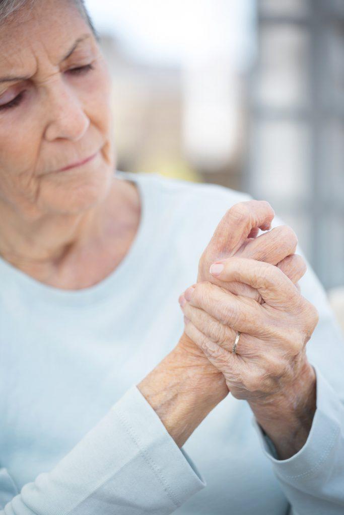 Senior woman massaging painful hand joints.