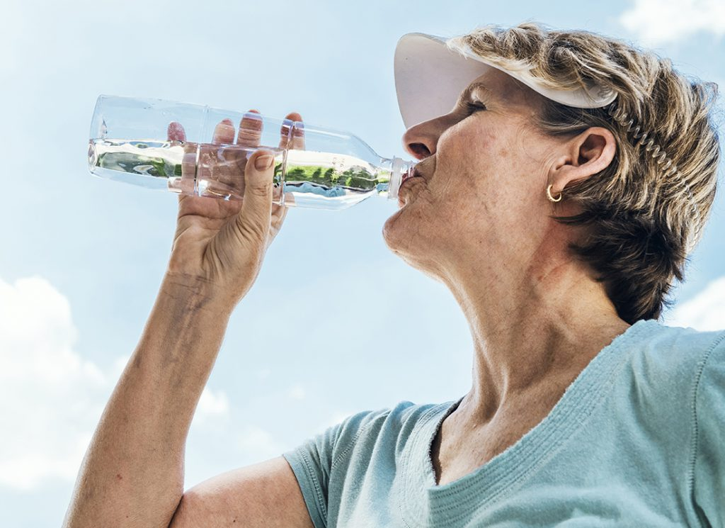 Senior woman drinking from water bottle
