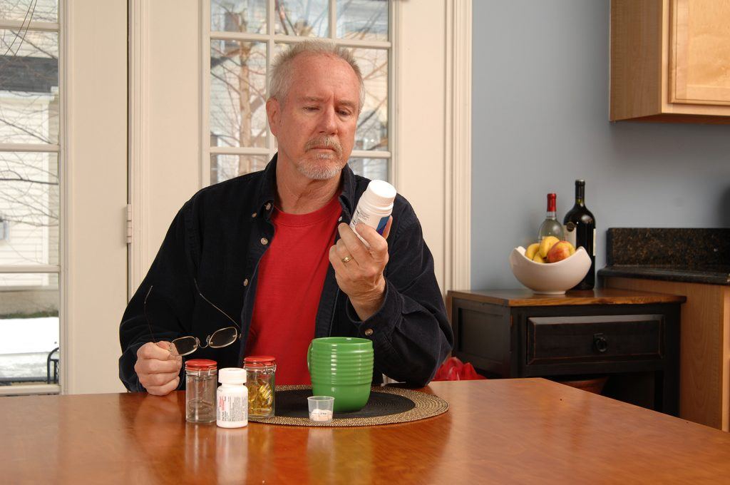 Senior man reading medicine bottle label at kitchen table.