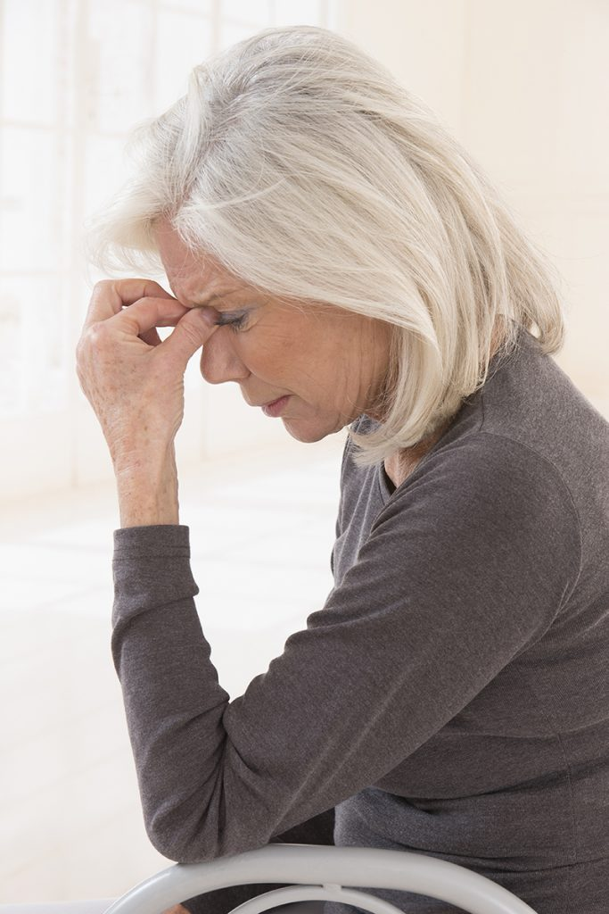 Senior woman in grey sweater holding her head with eyes closed in pain.