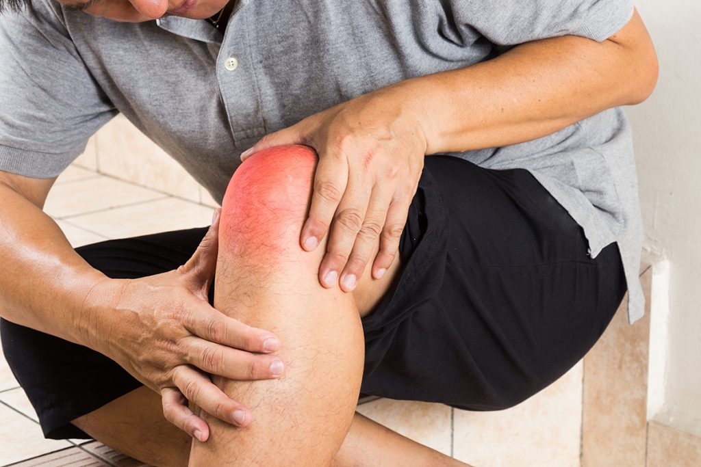 Senior man holding a painful knee joint.
