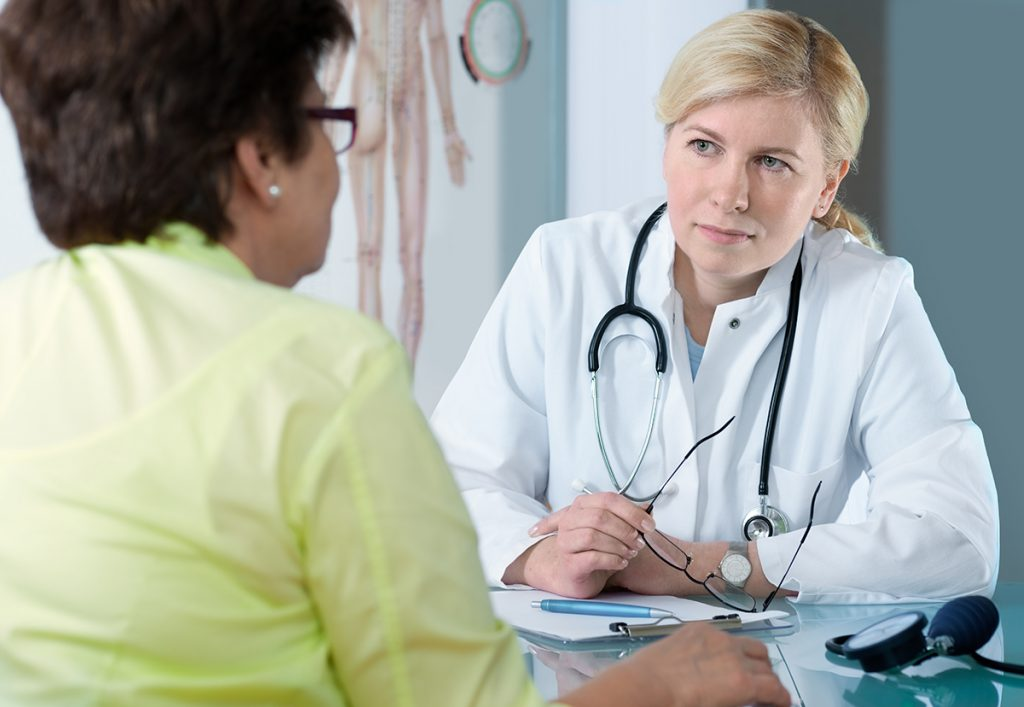 Senior patient discussing medical problems with concerned physician.