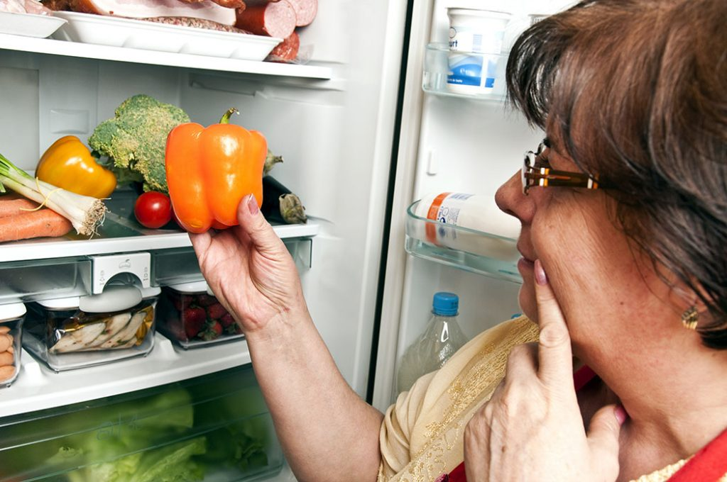Woman opens the refrigerator and wondering what she is looking for.