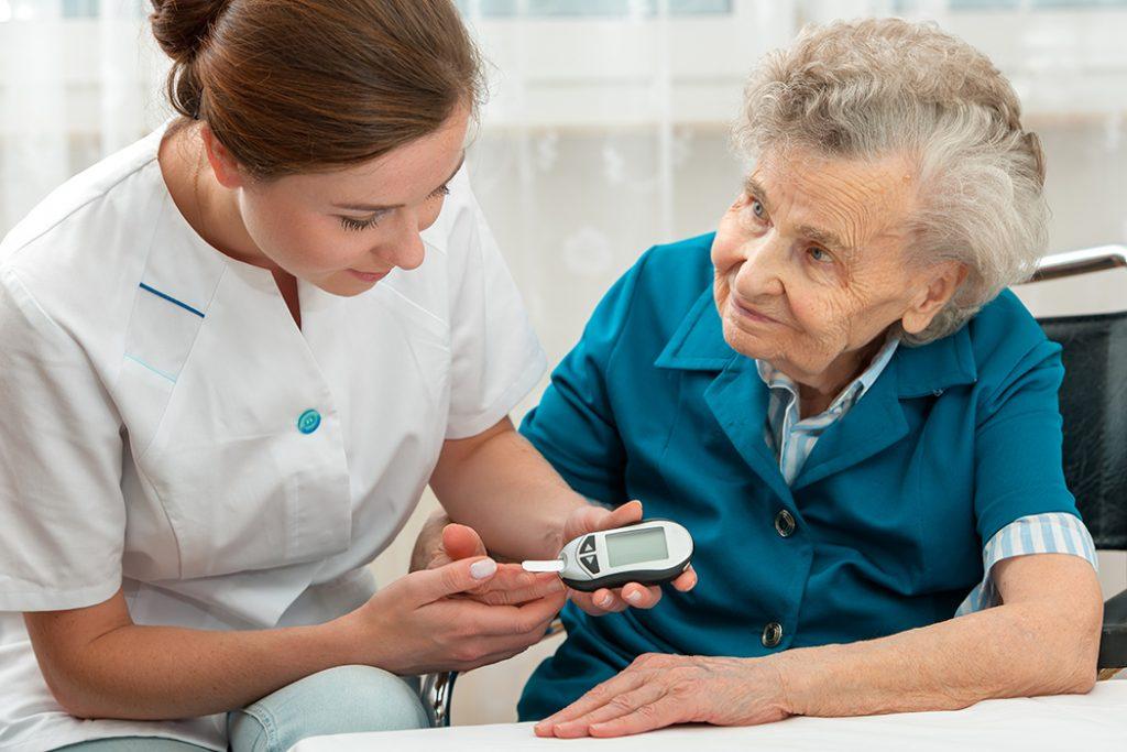 Nurse helping patient measure blood sugar level.