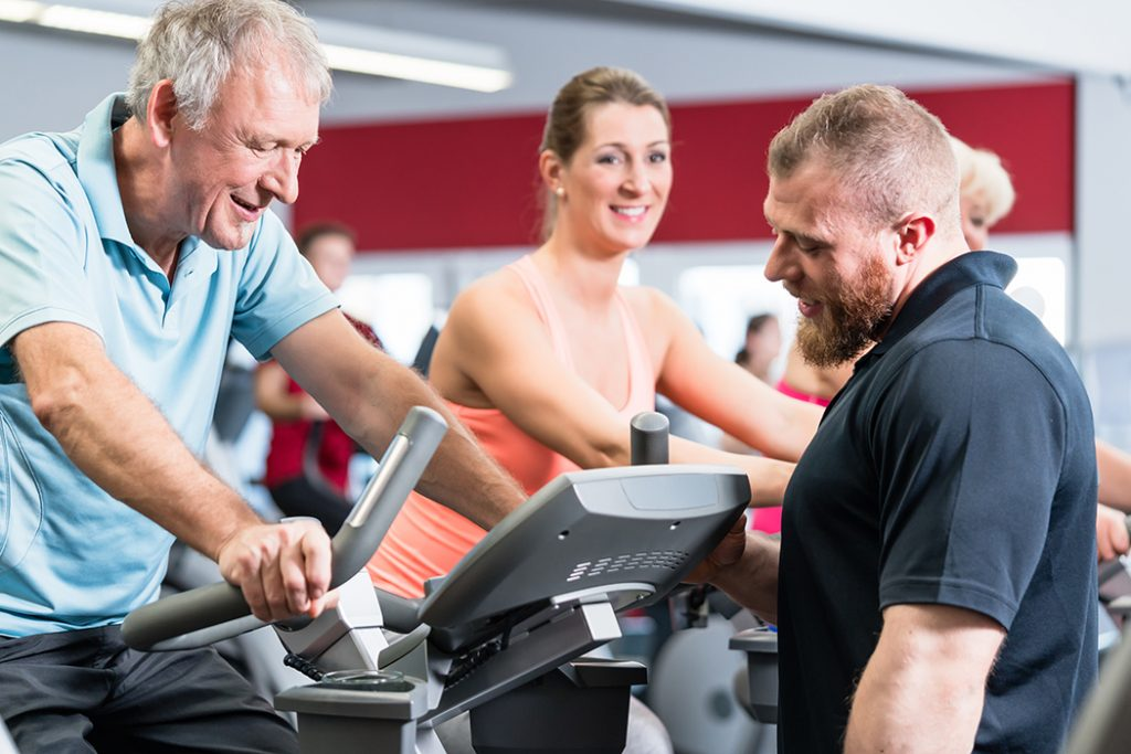 Group spinning with personal trainer in gym