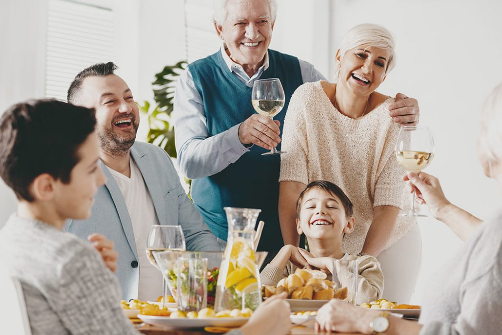 Smiling grandfather and grandmother making toast during family meeting with happy kid