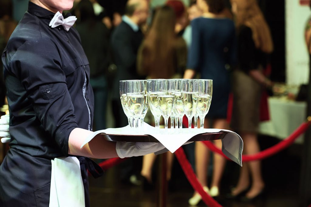 Waiter holding a tray with glasses of vine at party
