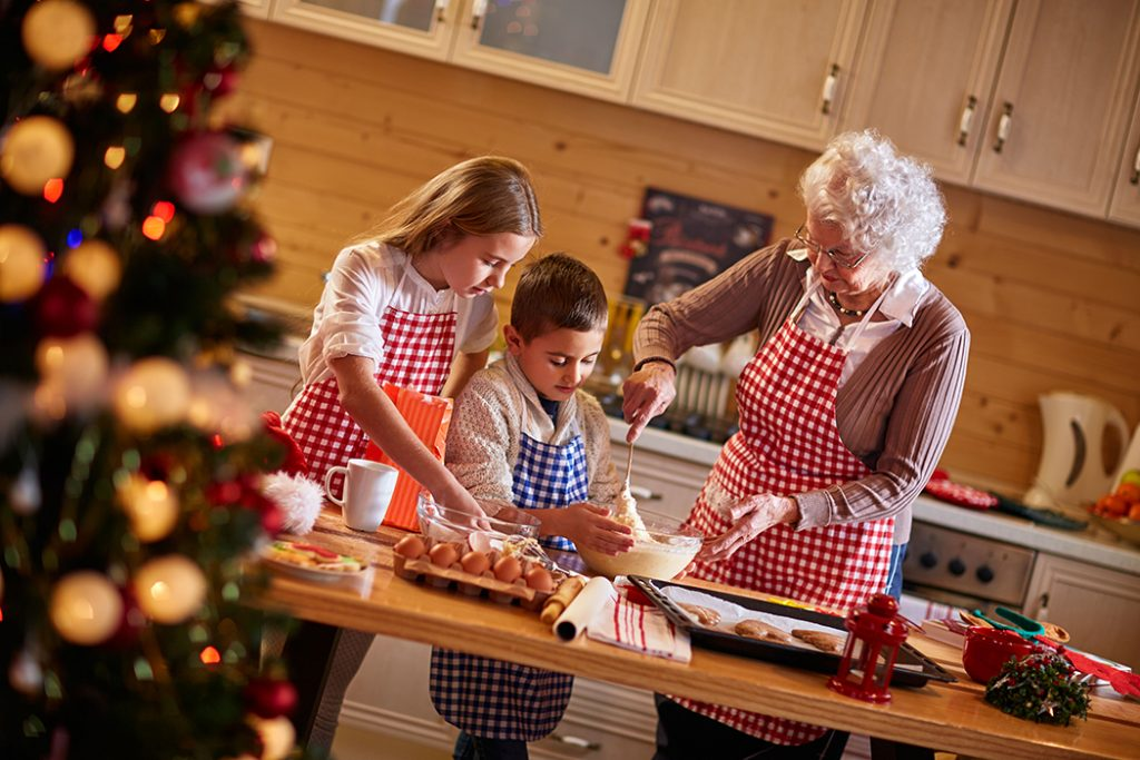children and grandmother preparing Christmas cookies.