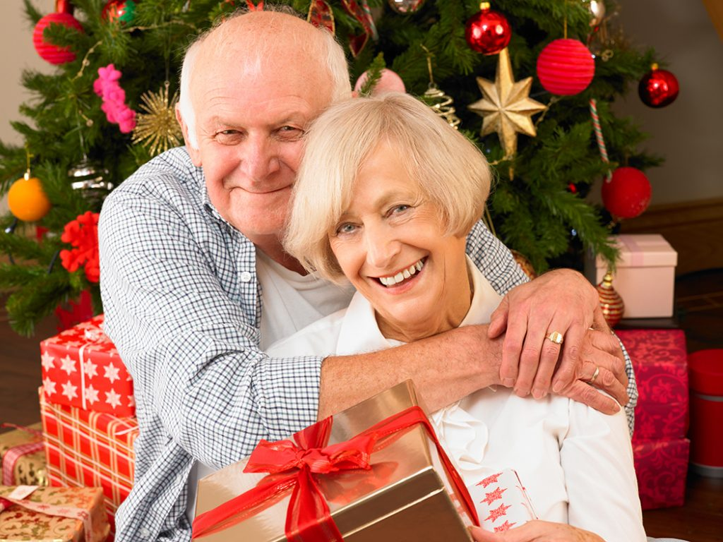 Senior couple hugging each other in front of the Christmas Tree.