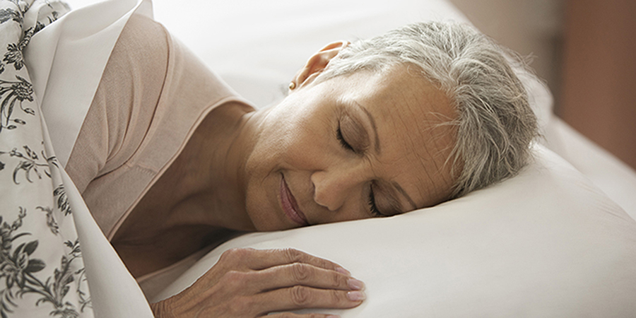 Woman peacefully sleeping in bed.