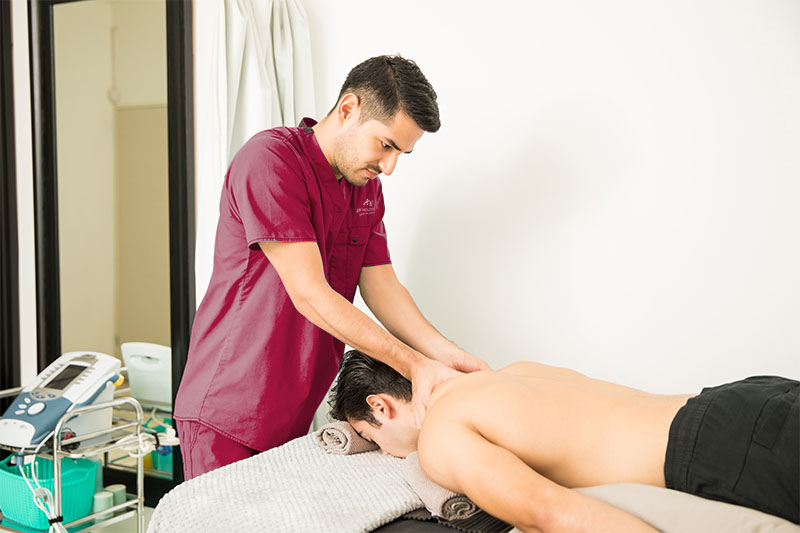Young man getting back and neck therapy in therapy clinic.