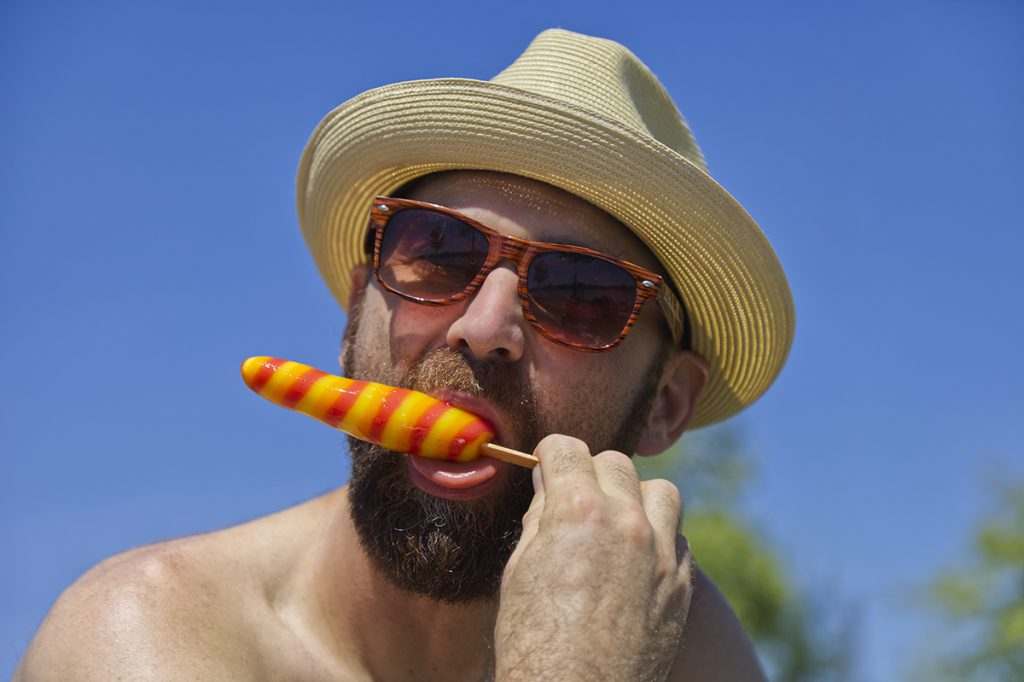 Senior man eating a popsicle on a very hot day.