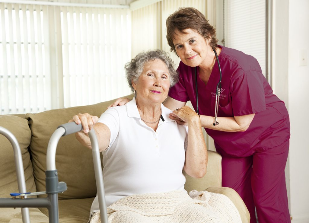 Nurse and patient smiling in a home setting.