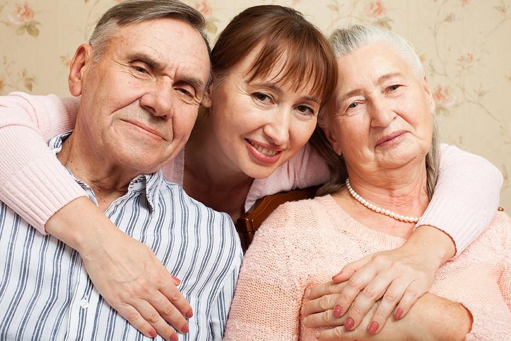 Senior couple smiling with adult daughter hugging them both.