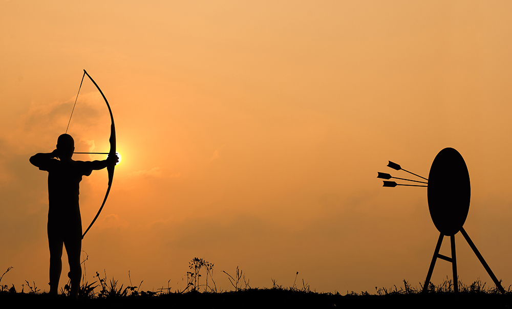 Silhouette archery shoots a bow at the target in sunset sky and cloud.