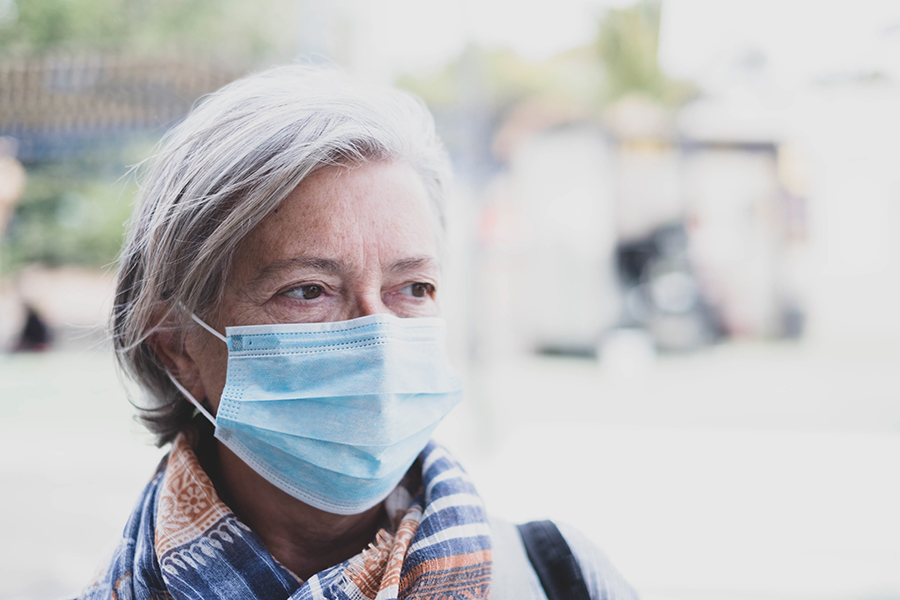 close up of face of mature woman looking away wearing medical mask.a