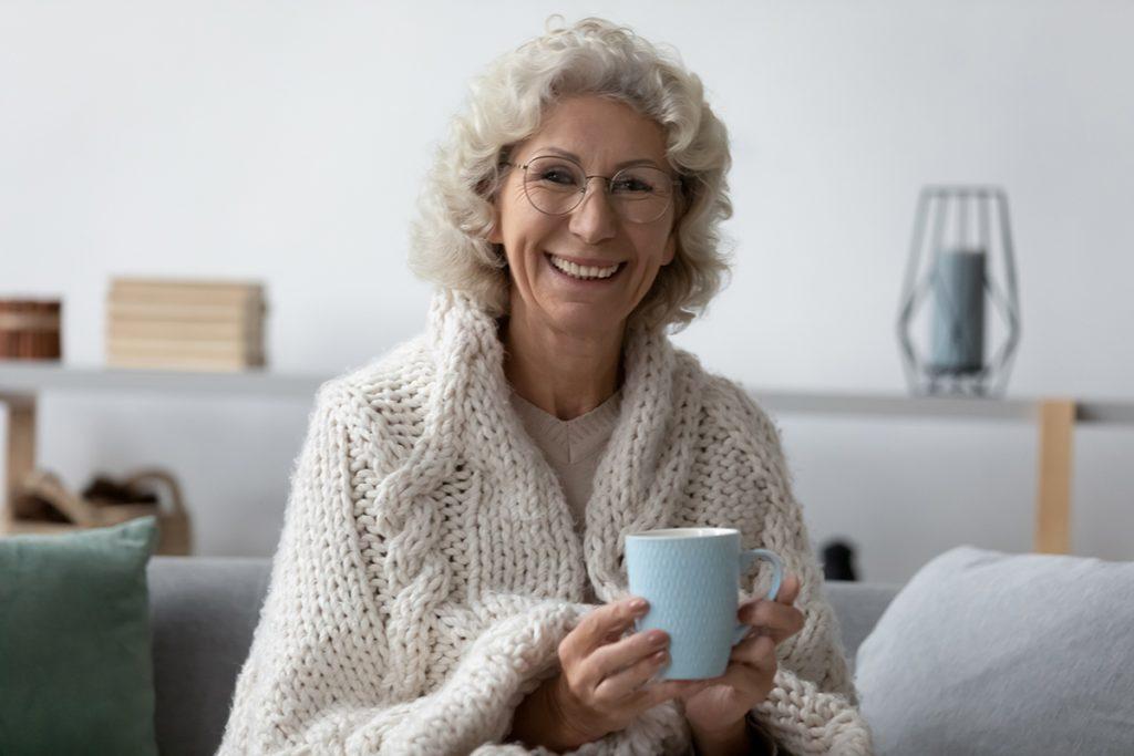 Head shot portrait smiling mature woman wearing glasses holding mug