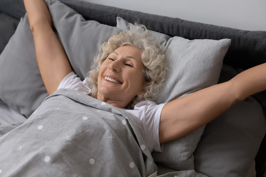 Elderly woman lying in bed stretched arms enjoy good morning